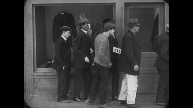 1921 man (buster keaton) argues his way to the back of the breadline where, foiled by mannequins, he misses food - oblivious stock videos & royalty-free footage