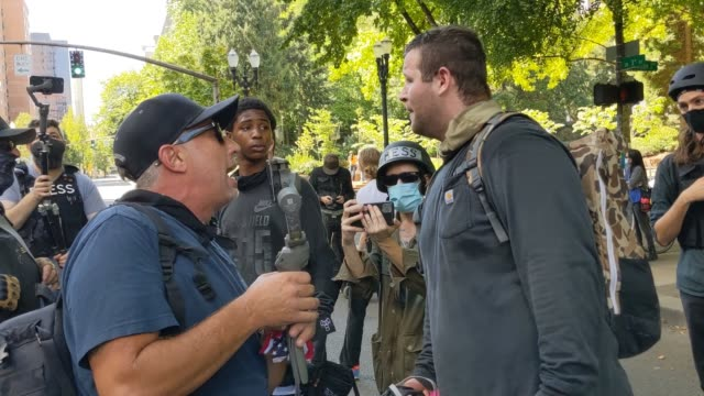 man argues with people as right wing groups and portland anti-police protesters face off in front of the multnomah county justice center on august... - portland oregon stock videos & royalty-free footage