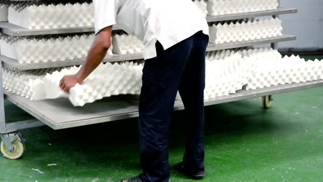 Man arrange white latex pillow to the shelf in factory