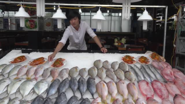 A man arranges a fish buffet in Seafood restaurant