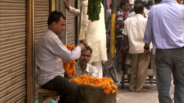 a man arranges garlands of orange flowers at the side of a narrow delhi street. - delhi stock videos & royalty-free footage
