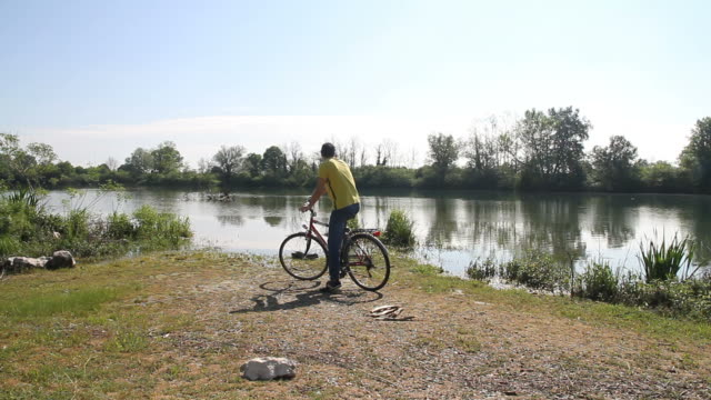 Man arrive at river with bicycle