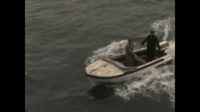 vídeos de stock e filmes b-roll de a man arrives late to a commercial shipping vessel by motor boat and climbs the ladder to get aboard film originates from the collection of emmy... - corda de trepar