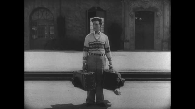 vídeos de stock e filmes b-roll de 1927 man (buster keaton) arrives on the busy clayton college campus - anticipation