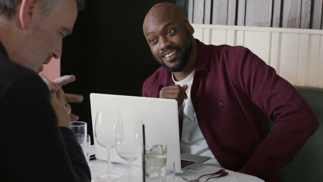 man arriving to restaurant with laptop and sitting down with colleague - interview stock videos & royalty-free footage