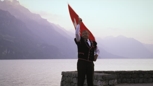 Man artfully twirls and throws Swiss flag