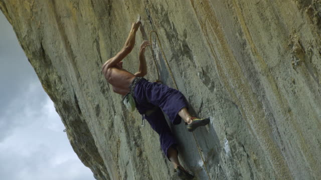 la ms man ascending rock face using finger-holds, falling off and hanging by rope, climbing back up / krabi, thailand - rock face stock videos & royalty-free footage