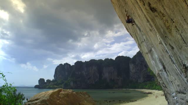 vidéos et rushes de ws man ascending rock face using finger-holds, falling, woman belays from below, beach in background / krabi, thailand - rock face