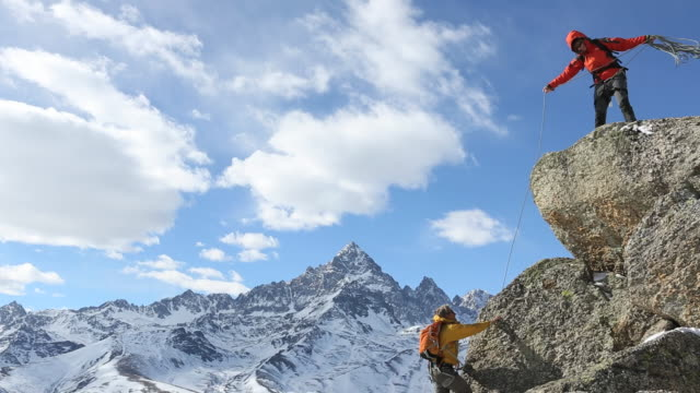 man ascends cliff with rope, leader offers assistance - moving up stock videos & royalty-free footage