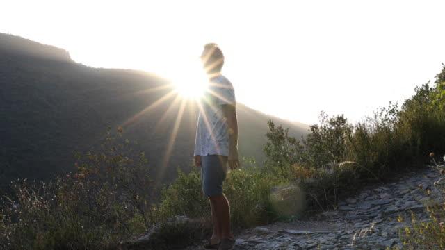 vídeos de stock, filmes e b-roll de man ascends cobblestone path above distant hillside, sunrise - só um homem maduro