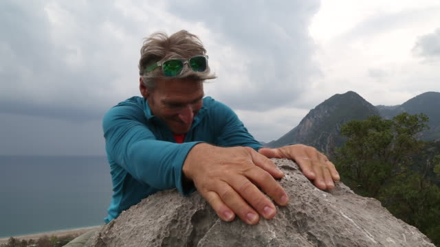 man ascends summit rock, above sea and mountains - top capo di vestiario video stock e b–roll