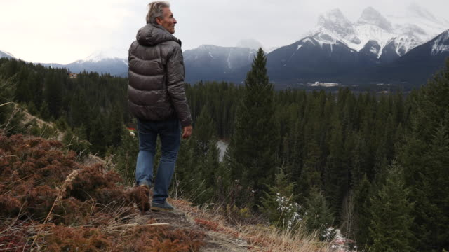Man ascends trail on mountain slope, looks off