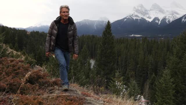 mann steigt weg am berghang, sieht aus - 55 59 jahre stock-videos und b-roll-filmmaterial
