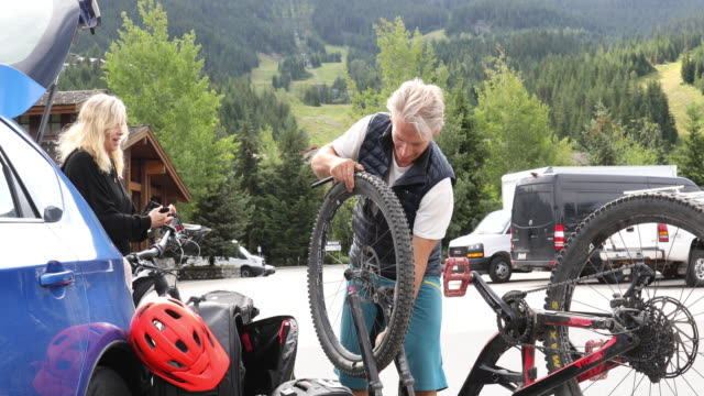 vídeos de stock, filmes e b-roll de o homem monta a bicicleta ao lado do carro, no lote - equipamento esportivo