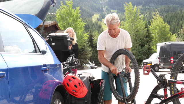 man assembles bike beside car, in lot - boot stock videos & royalty-free footage
