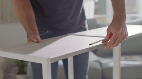 vídeos y material grabado en eventos de stock de man assembles flat pack shelf in home living room. - estante muebles