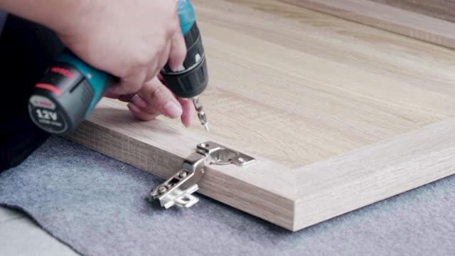 Mann baut Möbel mit einem Kraft-Schraubendreher