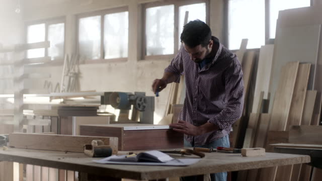 man assembling drawer at furniture workshop - installing stock videos and b-roll footage