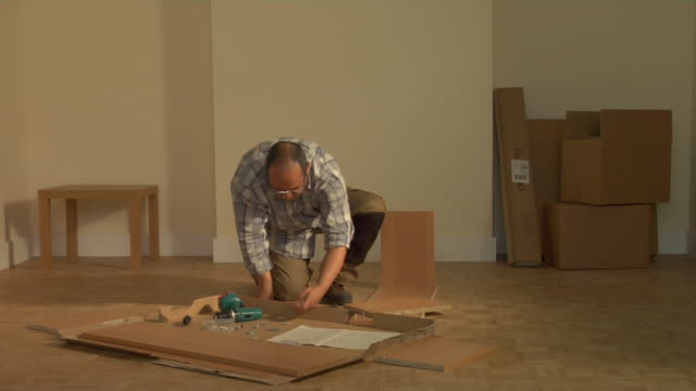 t/l ws man assembling flat pack shelves in empty room, london, england - furniture stock videos & royalty-free footage