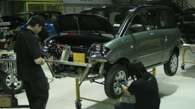 stockvideo's en b-roll-footage met ms man assembling front of electric car on production line, woman attaching wheel to wheel base, man inspecting car in background, st. jerome, quebec, canada - autofabriek