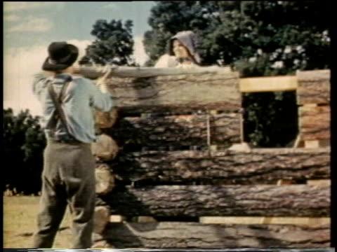 1941 ms man assembling log cabin / united states  - hängslen bildbanksvideor och videomaterial från bakom kulisserna