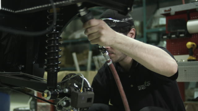 CU Man assembling shocks on electric car on assembly line, St. Jerome, Quebec, Canada