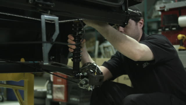 MS Man assembling shocks on electric car on assembly line, St. Jerome, Quebec, Canada
