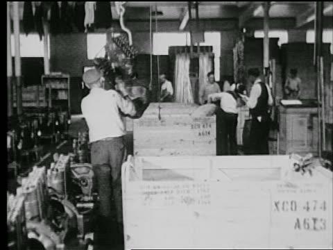 stockvideo's en b-roll-footage met b/w 1927 man assisting crane put engine in crate / industrial - 1927