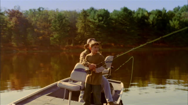 vídeos de stock, filmes e b-roll de ms, man assisting grandson (10-11 years) in casting fishing line while fly fishing on lake, usa, pennsylvania - 10 11 years