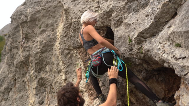 man assisting teenage girl in free climbing at nature - free climbing stock videos & royalty-free footage
