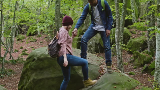 man assisting woman walking on boulder in forest - mid adult couple stock videos & royalty-free footage
