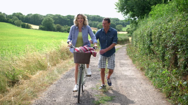 stockvideo's en b-roll-footage met man assisting woman while cycling - hulp