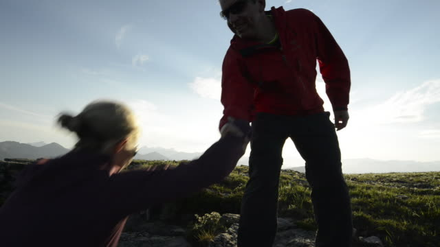 man assists woman onto grassy ridgecrest, above mountains - a helping hand stock videos & royalty-free footage