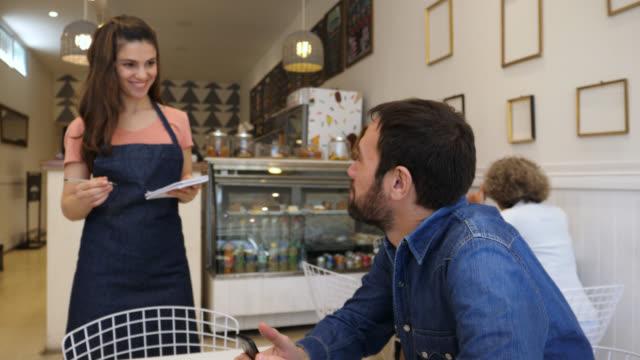 man på ett bageri som chattar på sin smartphone och vänlig servitris gå upp till honom att ta hans beställning - servitris bildbanksvideor och videomaterial från bakom kulisserna
