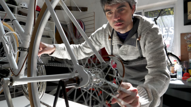 man at a bicycle repair shop checking the chain while moving the back wheel of the bicycle - repair shop stock videos & royalty-free footage