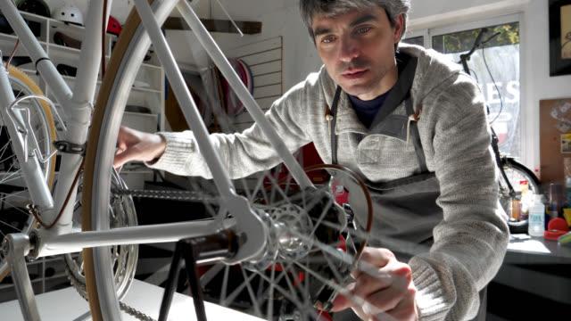 vidéos et rushes de homme à un atelier de réparation de vélo vérifiant la chaîne tout en déplaçant la roue arrière du vélo - entretien