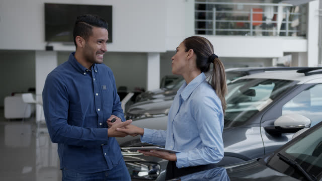 man at a car dealership ready to take the car for a test drive as saleswoman notes something on tablet and hands him the key - contract stock videos & royalty-free footage
