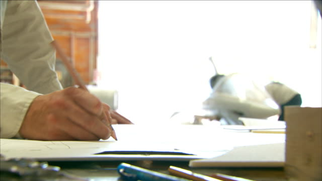 a man at a drafting table in a hangar draws with a pencil on paper. - 図面点の映像素材/bロール