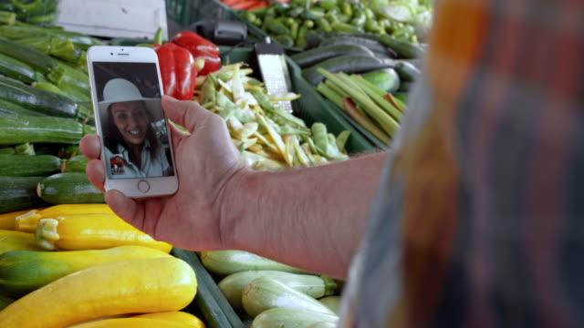vídeos y material grabado en eventos de stock de hombre en mercado en videocall con esposa - miembro humano