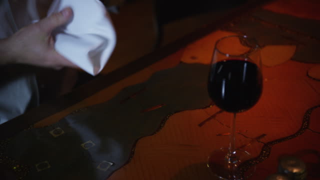 man at a restaurant table, he unwraps the silverware from a cloth napkin; glass of wine sets on table. - マナー点の映像素材/bロール