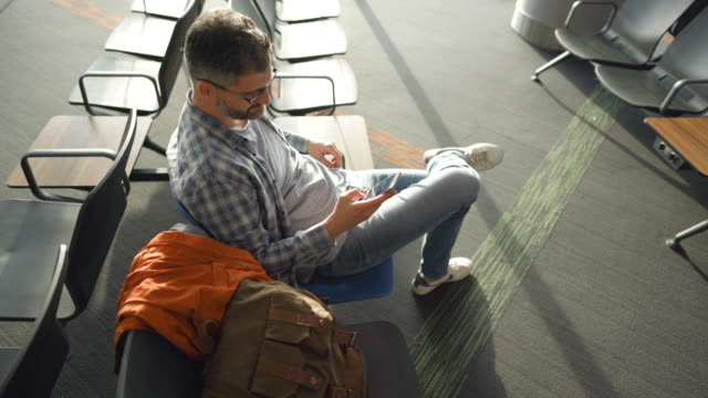 man at airport lounge using mobile phone - luggage stock videos & royalty-free footage