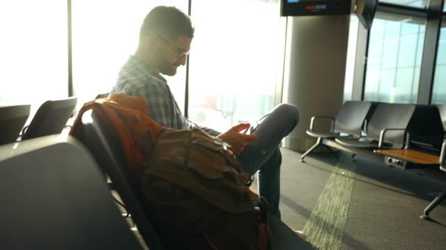 vídeos y material grabado en eventos de stock de hombre en el salón del aeropuerto utilizando el teléfono móvil - rucksack