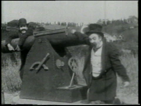 stockvideo's en b-roll-footage met b/w 1915 man at cannon shouting to someone offscreen / 2nd man leaning on cannon / feature - 1915