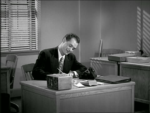 b/w 1949 man at desk talking on phone / hangs up + writes note / colleague enters + they talk - 1949 stock videos & royalty-free footage