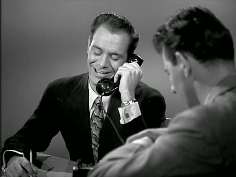 b/w 1949 man at desk talking on telephone + hangs up / talks to other man in foreground - 1949 stock videos & royalty-free footage