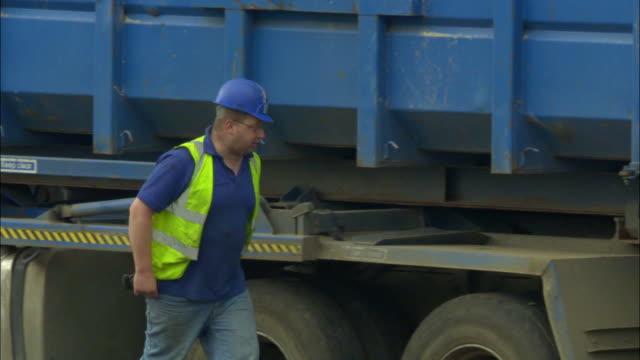 vidéos et rushes de ms, pan, man at dump truck in landfill site, ardley, oxfordshire, united kingdom - camion poubelles