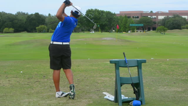 man at golf practice course for golfing at driving range practicing drives and working on game of golf - driving range stock videos & royalty-free footage