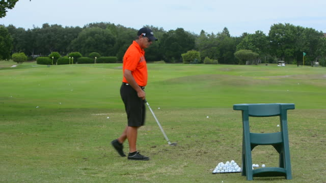 man at Golf practice course for golfing at driving range practicing drives and working on game of golf