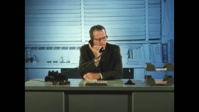 man at green desk in blue light answers telephone - green colour stock videos & royalty-free footage