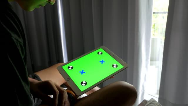 stockvideo's en b-roll-footage met man thuis en met behulp van de tablet met groen scherm - ledematen lichaamsdeel